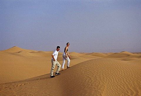 Young man and woman walk up sand dunes in the Sahara Desert, Morocco